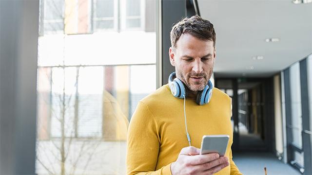 Kille med mobil och hörlurar