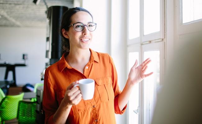 Kvinna-haller-kaffekopp-kontor