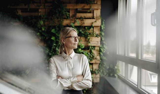 Kvinna framför vägg av grönska