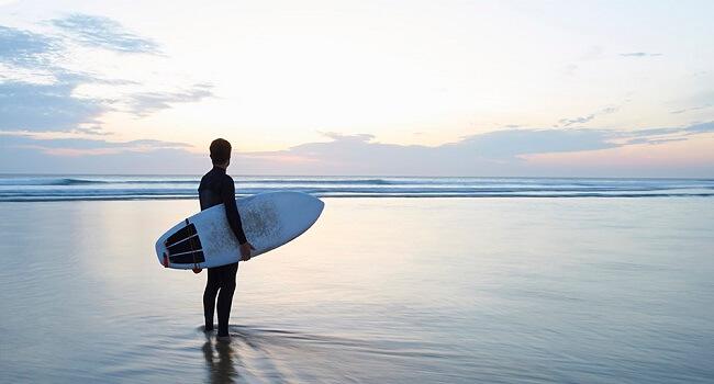 Surfare blickar ut mot havet