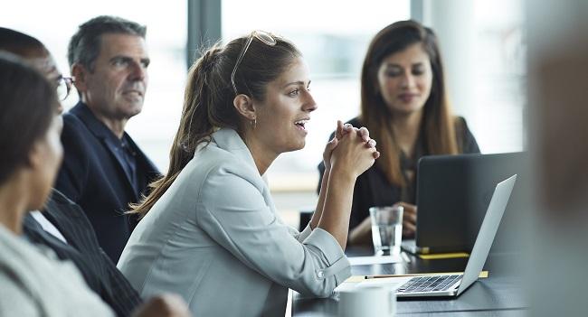 Framåtlutad kvinna på kontorsmöte