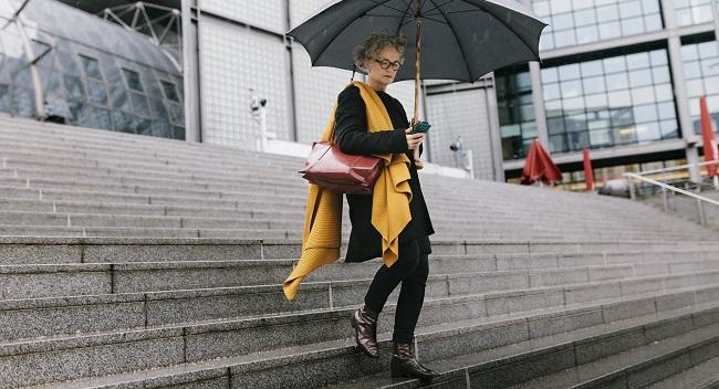 Kvinna med paraply går nerför en trappa