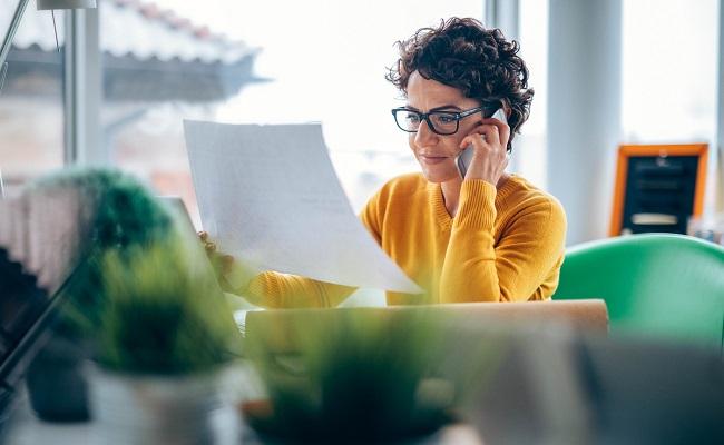 Kvinna-med-papper-och-mobil