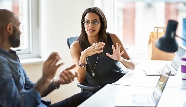 Kvinna och man diskuterar framför laptops