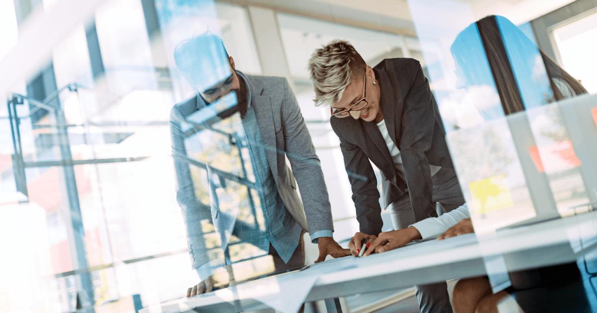 Två personer arbetar på ett bord i ett kontor