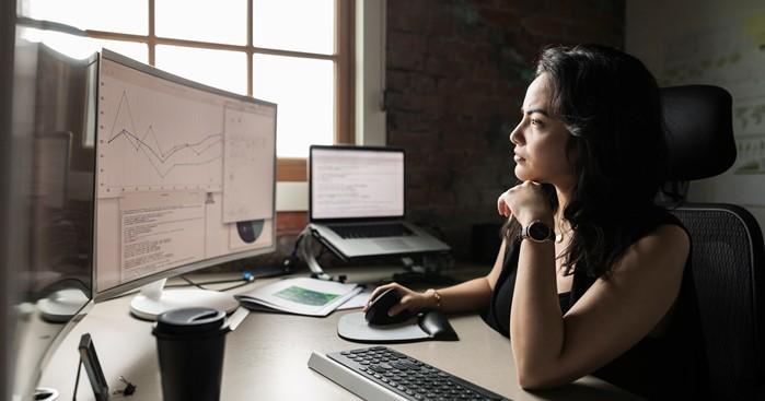 Kvinna vid datorn analyserar grafer