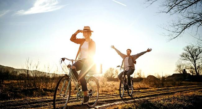Kvinna man cyklar på landsväg sommar