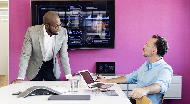 Två män i konferensrum med rosa vägg