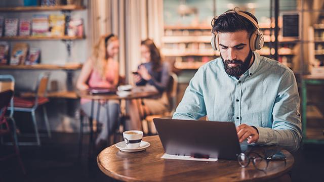 Man vid dator på café